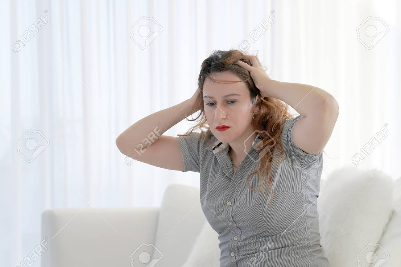 Woman suffering from headache migraine pain at home on sofa. Health problem, stress and depression. Female holds head with hand. Concept of health. - 124963841
