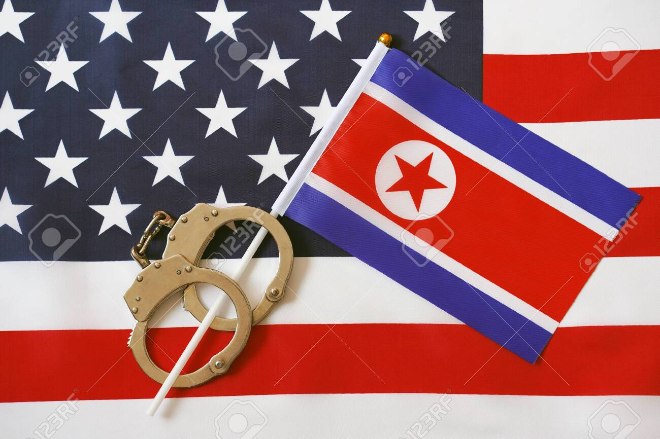 North Korea flag in handcuffs on the background of the American flag. US sanctions against North Korea. - 126669395