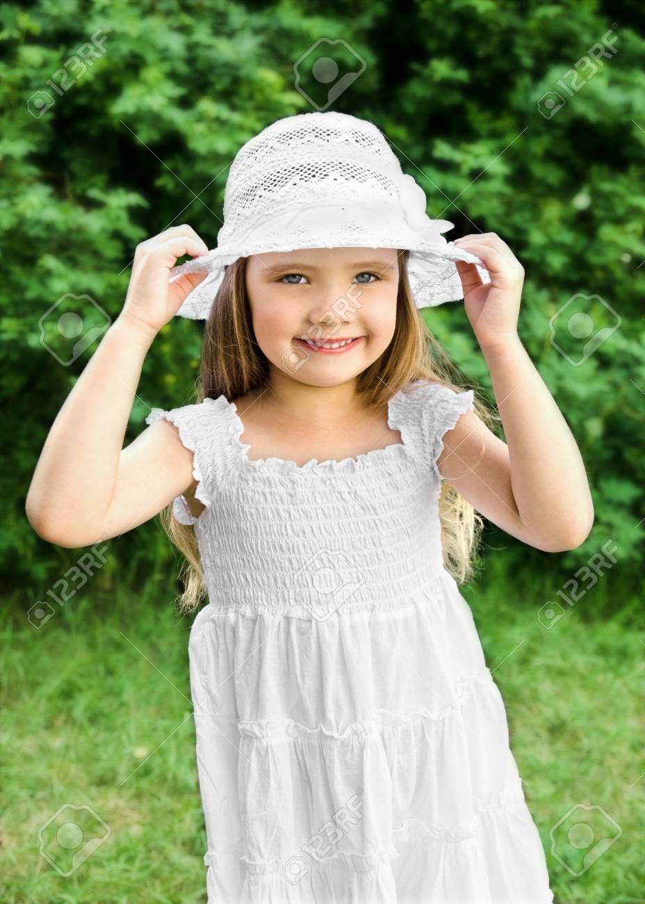 ed4cd468e Outdoor portrait of adorable smiling little girl in white dress and hat  Stock Photo - 20438685