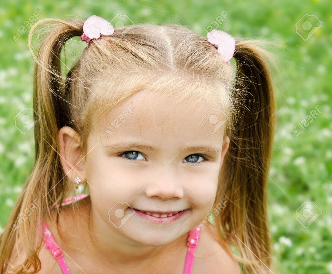 Cute smiling little girl on the meadow in summer day - 21090108
