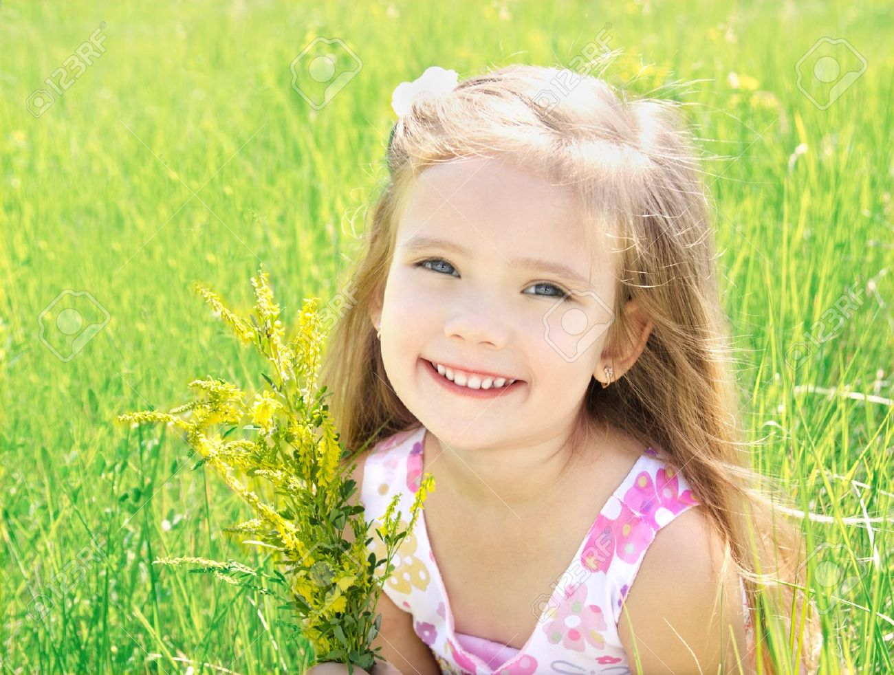 cute little girl on the meadow with flowers in summer day stock