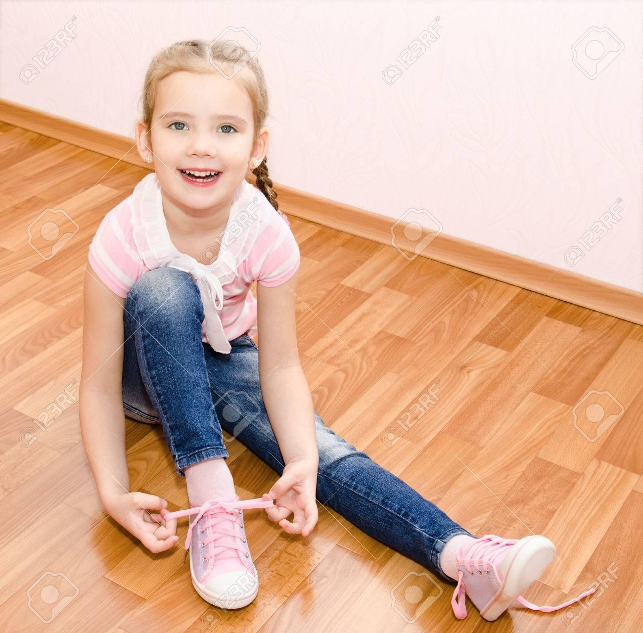 eac120a9224444 Nette lächelnde kleine Mädchen binden ihre Schuhe zu Hause Standard-Bild -  27737259