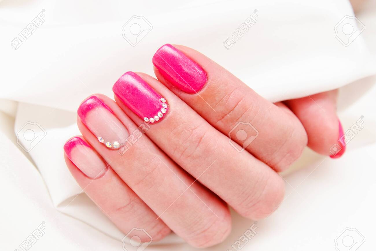 Woman's nails with beautiful manicure fashion design with gems pink color - 123365389