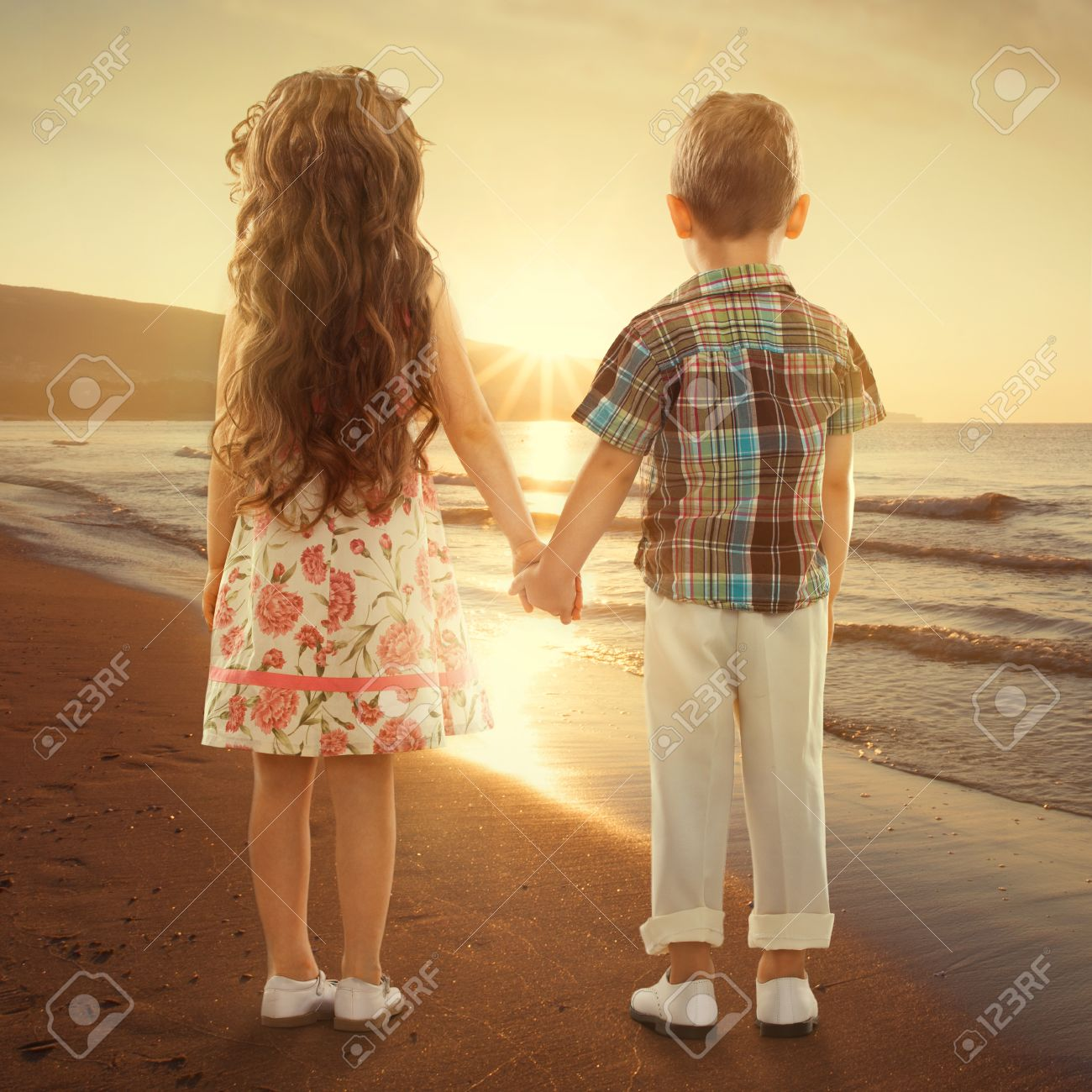 Back View Of Little Girl And Boy Holding Hands At Sunset Love