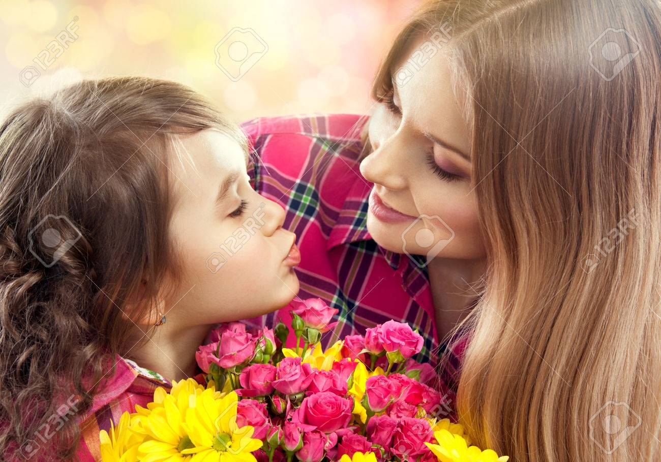 Daughter kissing happy mother with flowers  Mother s day concept  Family holiday Stock Photo - 26154291