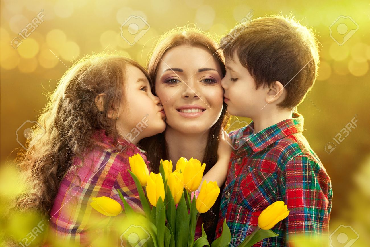 Portrait of children kissing her mother with flowers Spring, March 8, International Womens, Mothers day, family holiday - 26566505