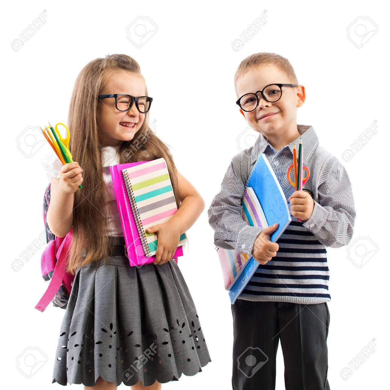 Two smiling school kids with colorful stationery, isolated on white background. School, education concept. - 31478086