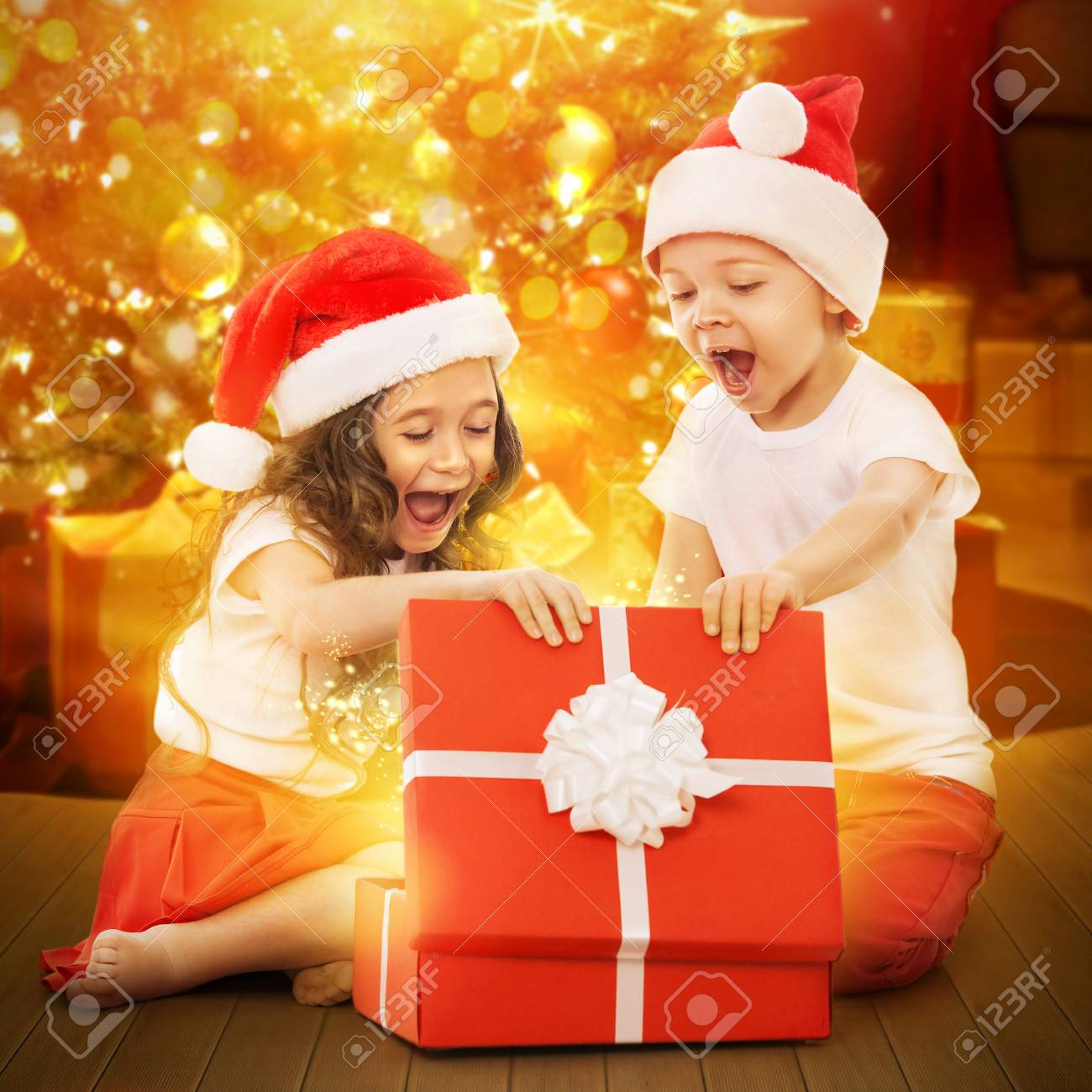 Colorful Christmas Background For Kids.Happy Kids In Santa Hat Opening A Gift Box With Colorful Lights
