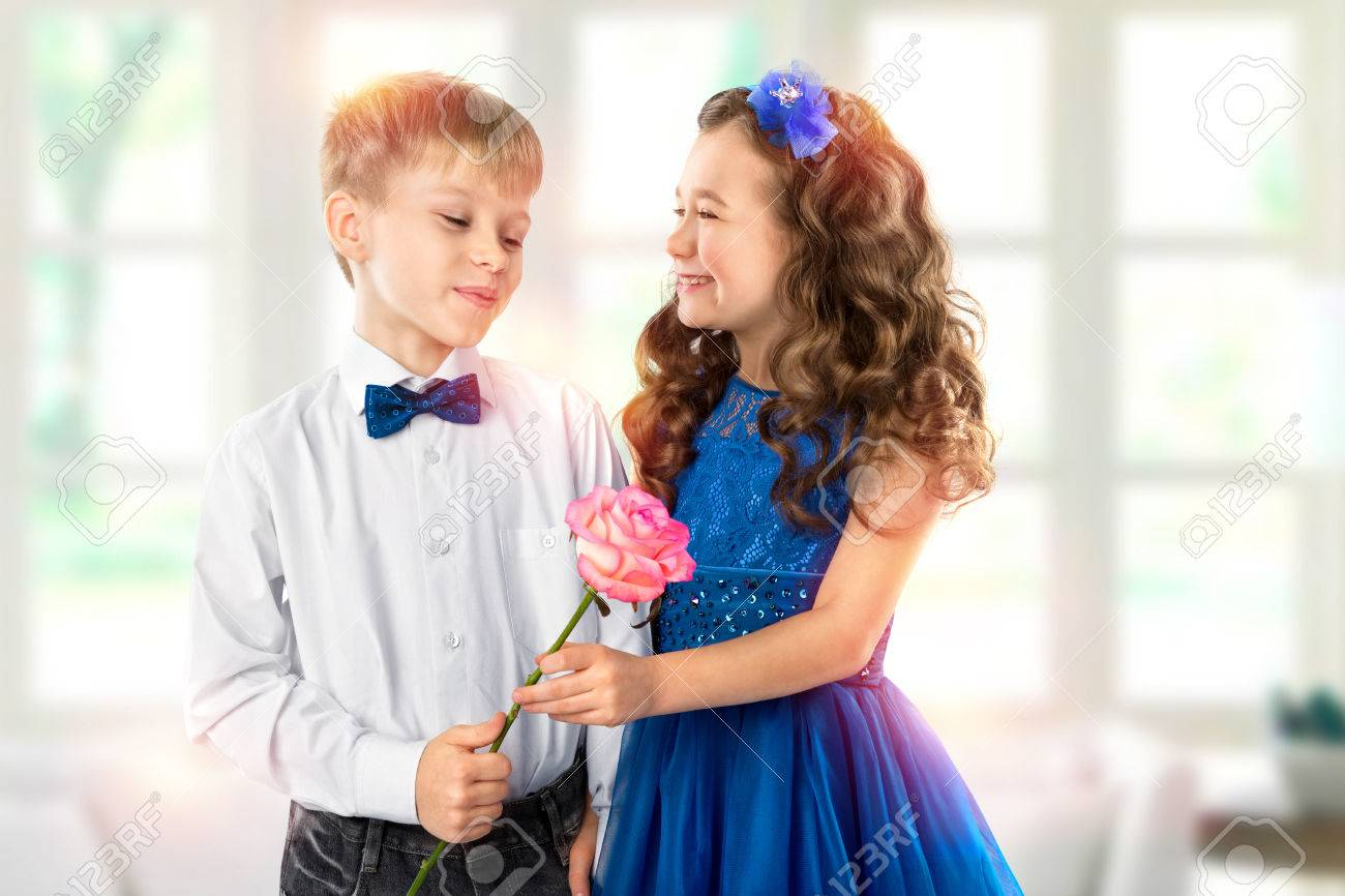 cute kids, boy gives a flower little girl. valentines day. child