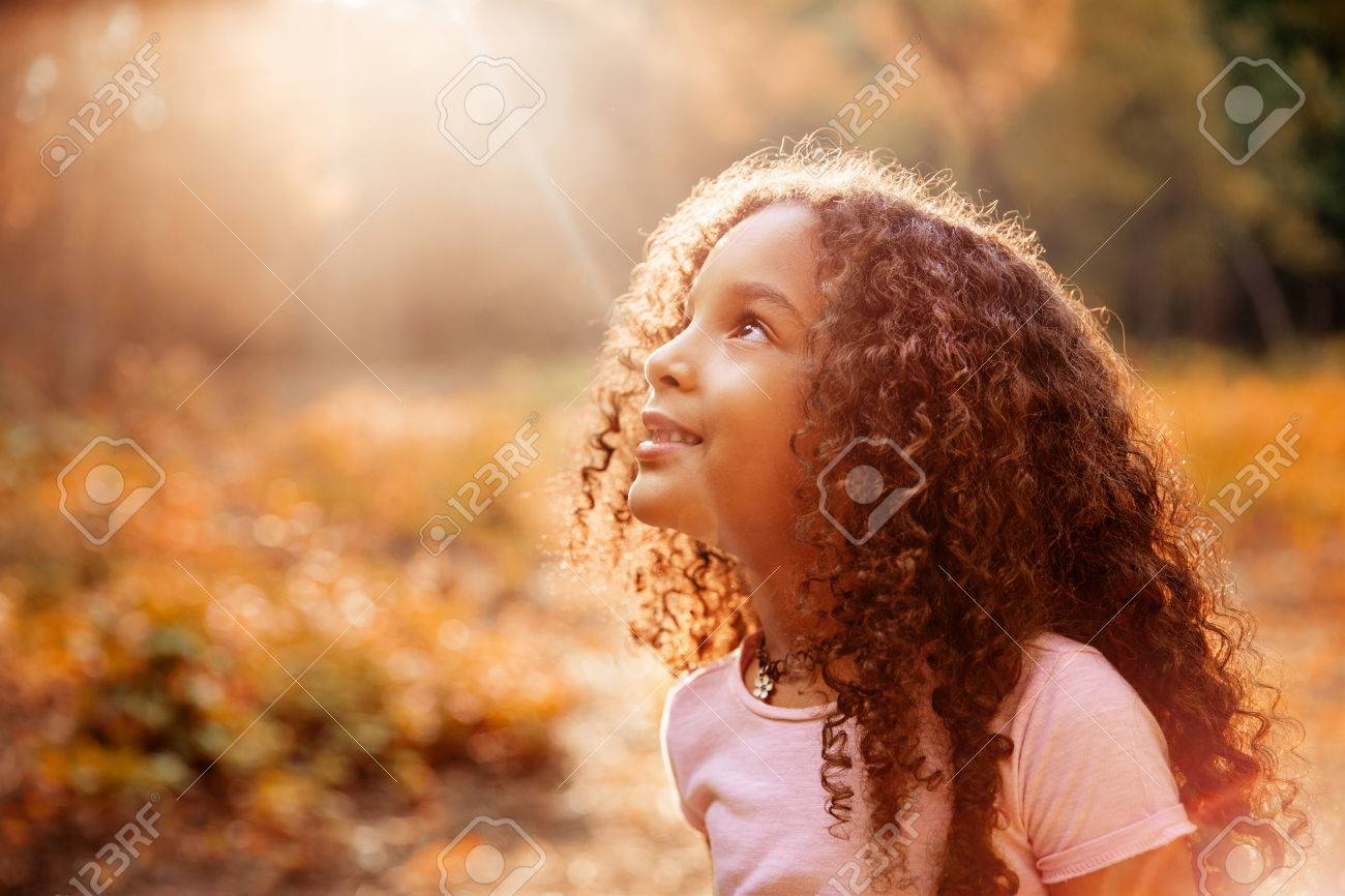 Afro american cute little girl with curly hair receives miracle sun rays from the sky - 86946267