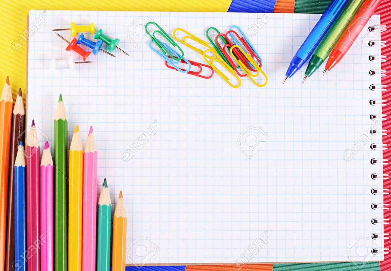 color pencils on multi colored paper with notebook stock photo