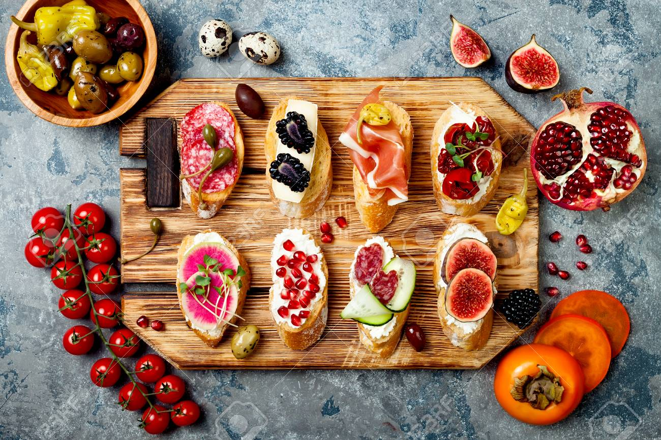 Appetizers table with italian antipasti snacks. Brushetta or authentic traditional spanish tapas set on wooden & Appetizers Table With Italian Antipasti Snacks. Brushetta Or.. Stock ...