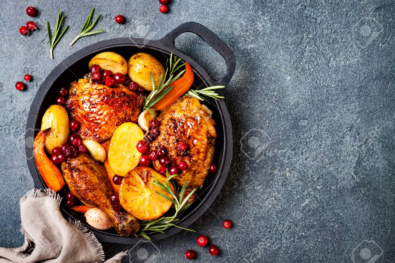 Roasted chicken legs with root vegetables, lemon, garlic, cranberry and rosemary on pan, on black slate stone background - 111462137