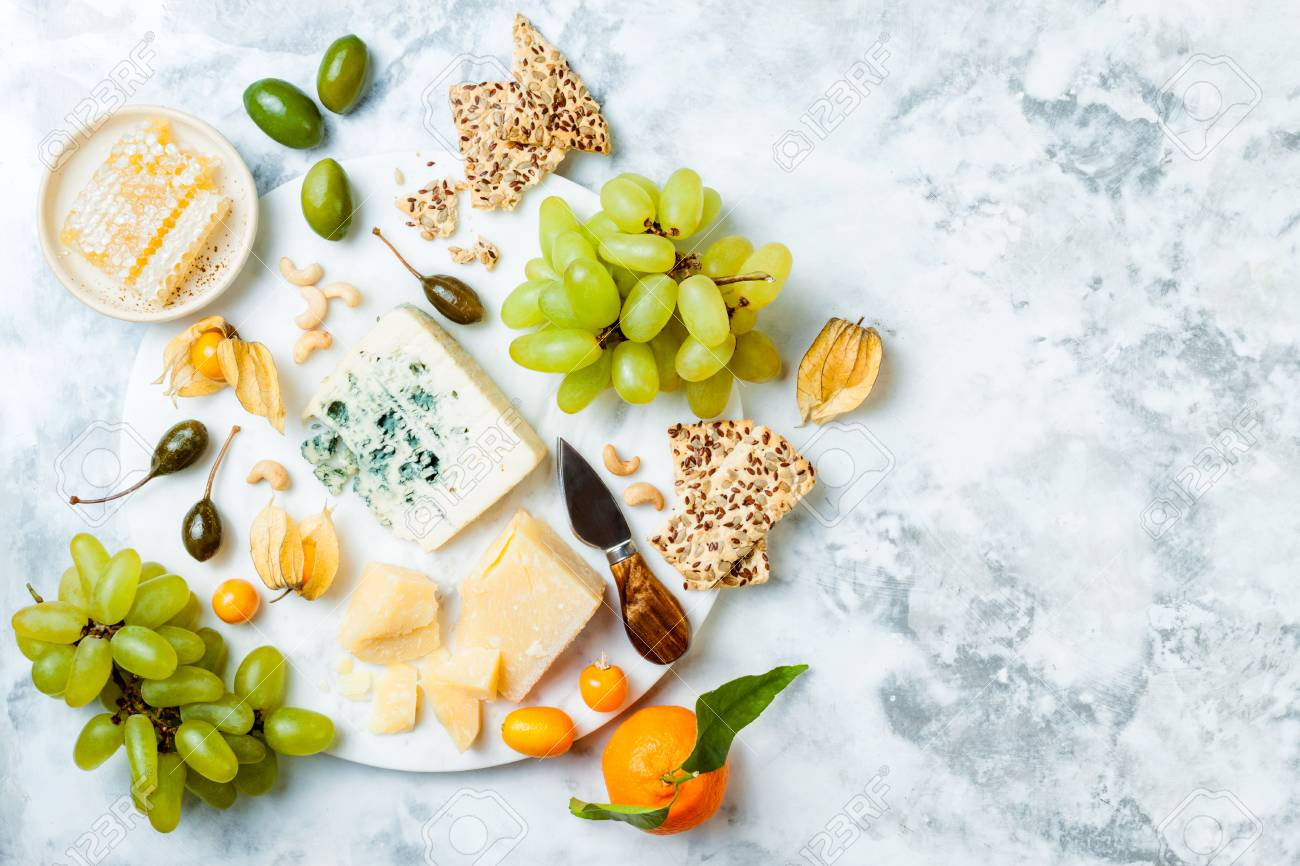 Cheese platter with different cheeses, grapes, nuts, honey. - 117900284