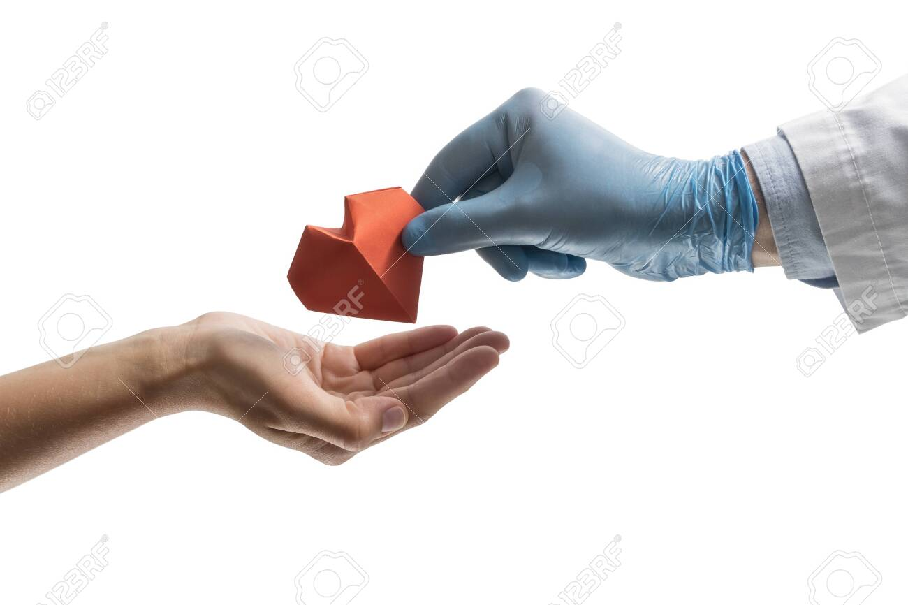 Doctor's hand gives a red paper heart to a woman. Image on isolated white background. Concept of salvation, donorship, helping hand. - 128338955