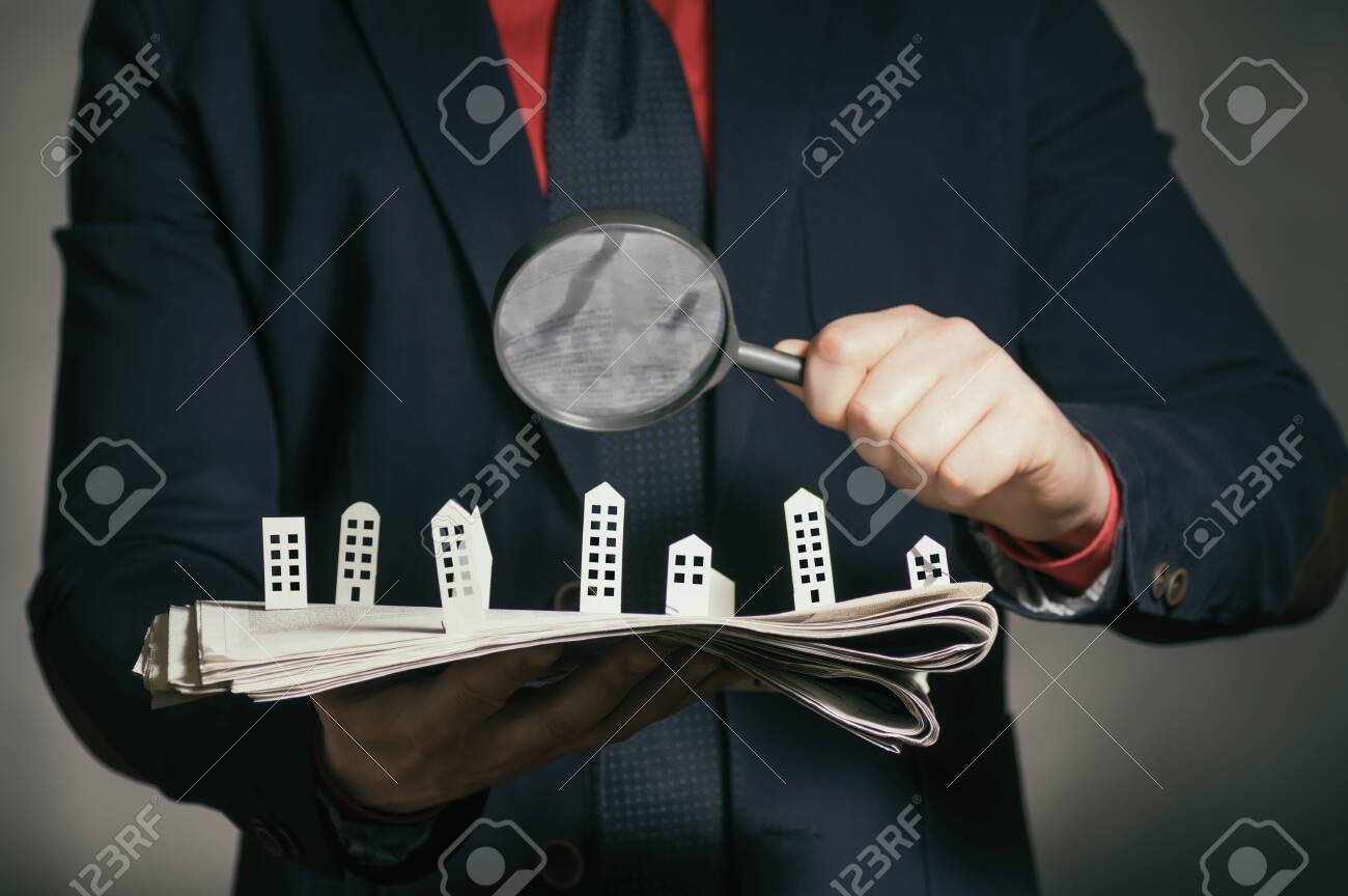 The man holds a newspaper with paper houses in front of yourself. Concept of real estate, housing construction. - 134847054