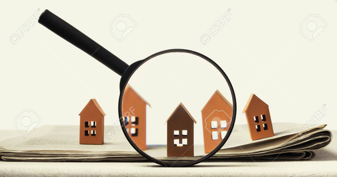 Magnifier in front of an open newspaper with paper houses. Concept of rent, search, purchase real estate. - 148978104
