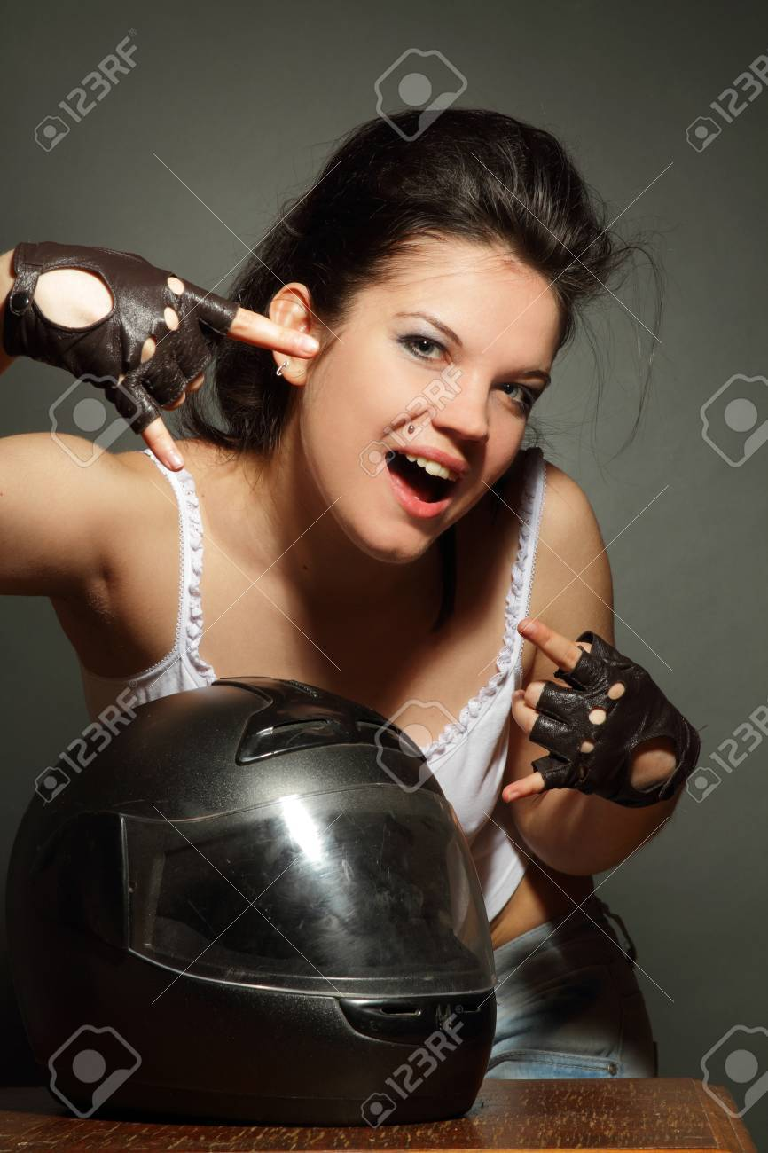 The girl with a motorcycle helmet on a gray background Stock Photo - 9675196