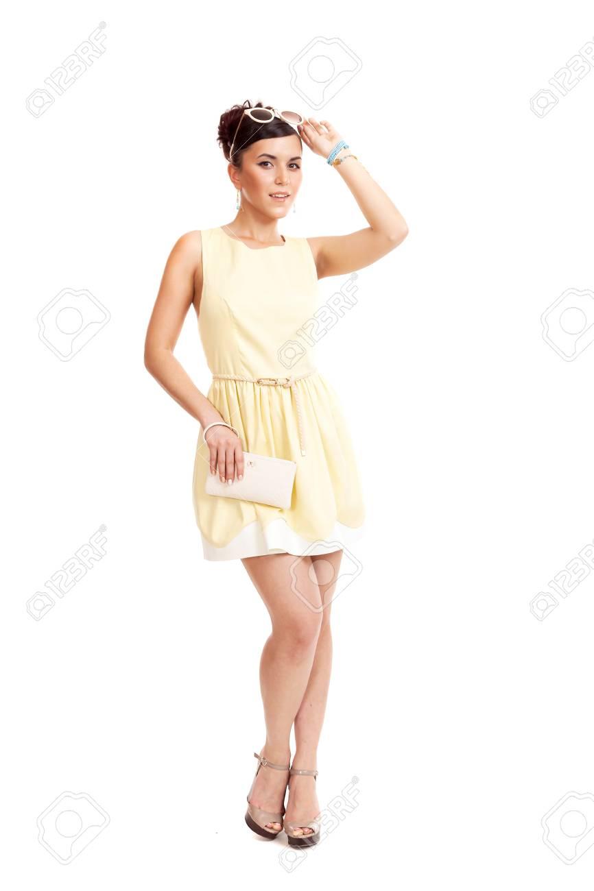 288891fc504b Archivio Fotografico - La giovane donna in occhiali da sole e in un abito  leggero su uno sfondo bianco