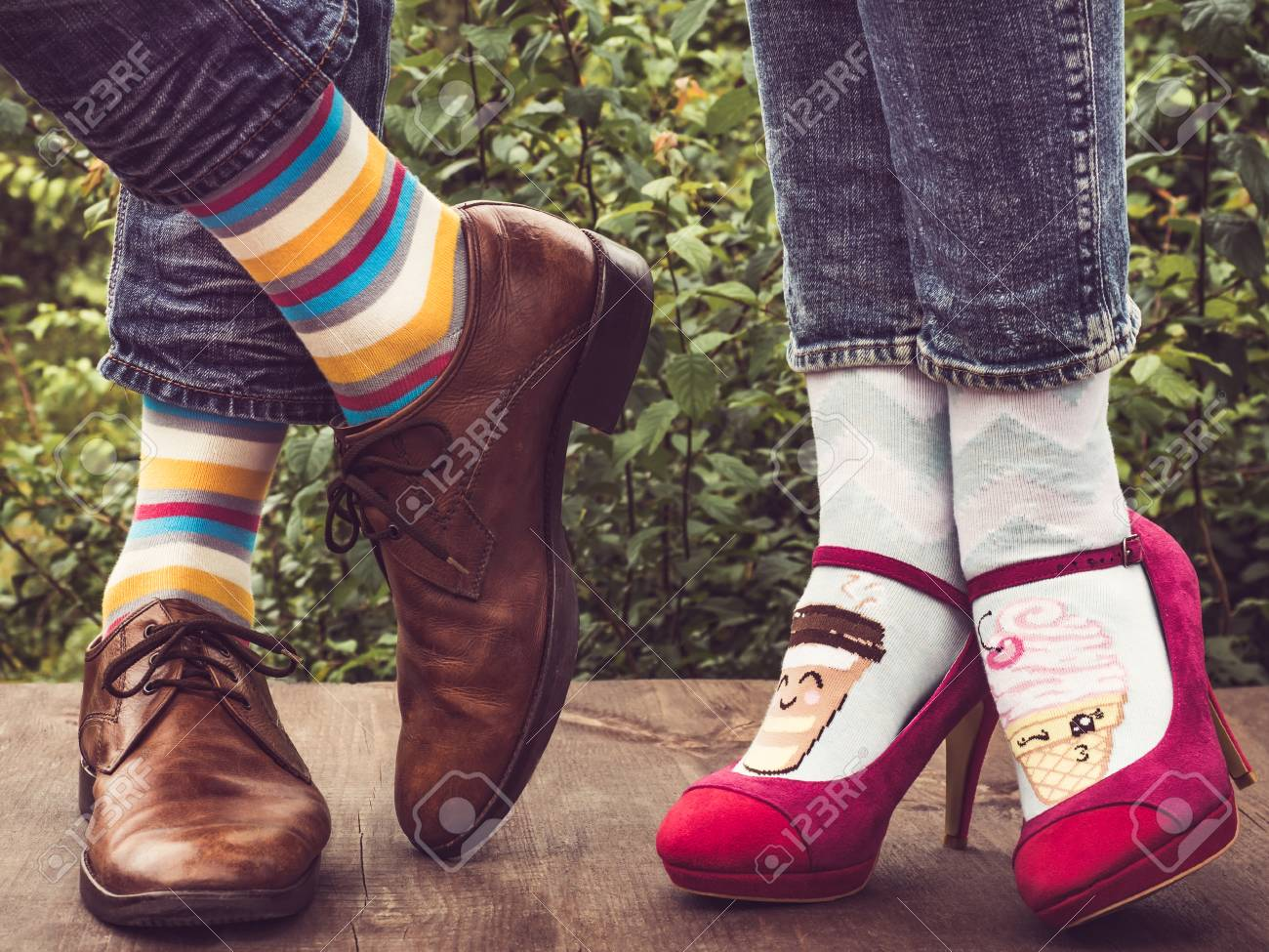 1806dd8d2 Men's and women's feet in stylish shoes, bright, colorful socks with  stripes patterns and pictures of ice cream on the wooden terrace on the  background of ...