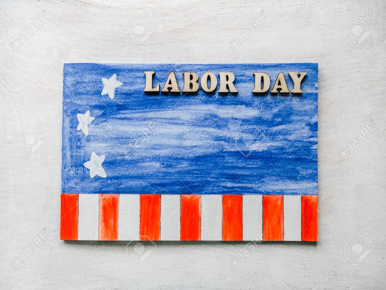 LABOR DAY. Notepad, American flag pattern and wooden letters of the alphabet on a white table. Close-up. Bright photo and space for your inscriptions. Congratulations to relatives, friends, colleagues - 122820959