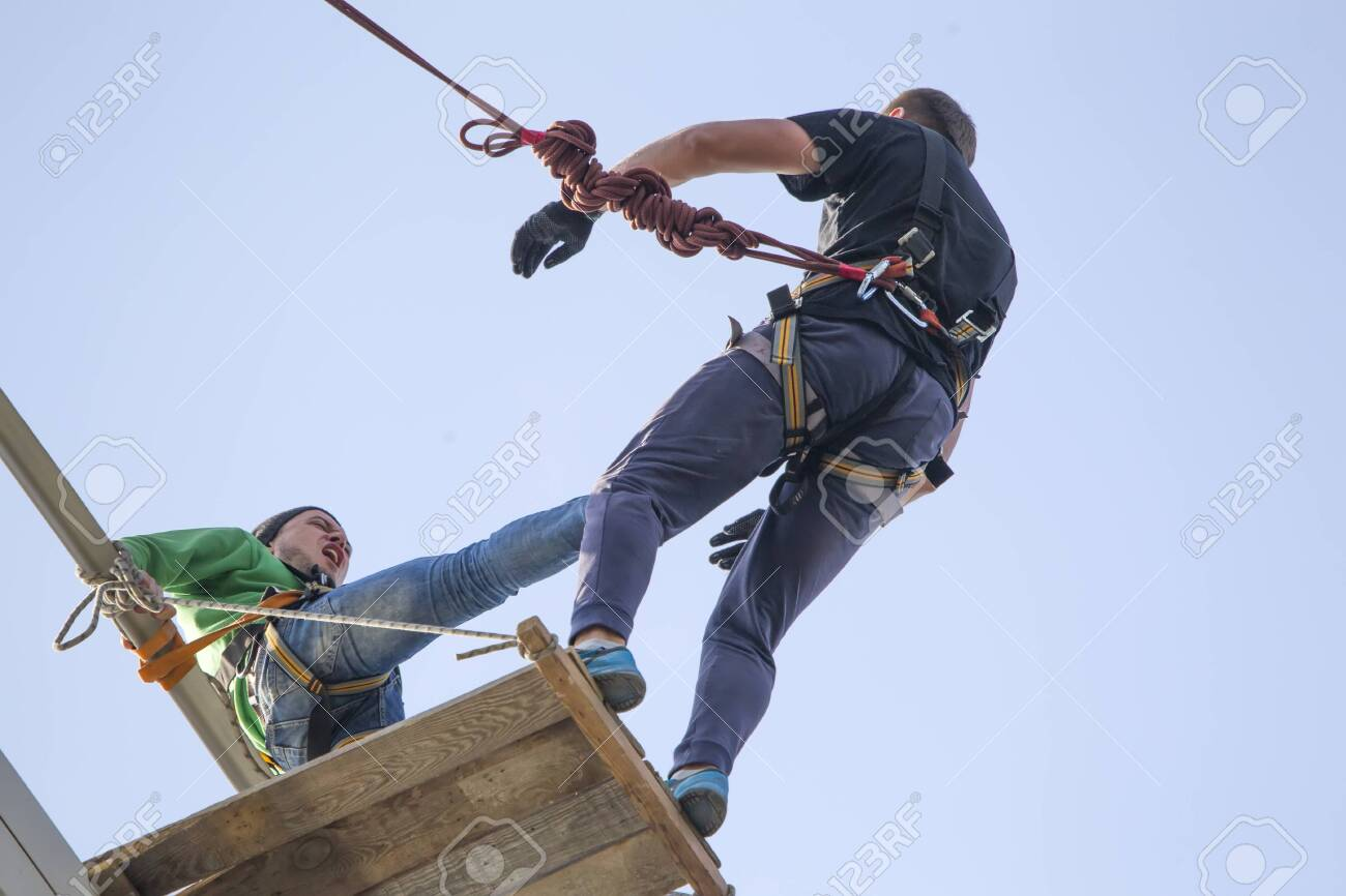 Belarus, Gomel, May 01, 2017.Jumping with a rope.A man pushes another man from the bridge. Engage in extreme sports. - 143989490