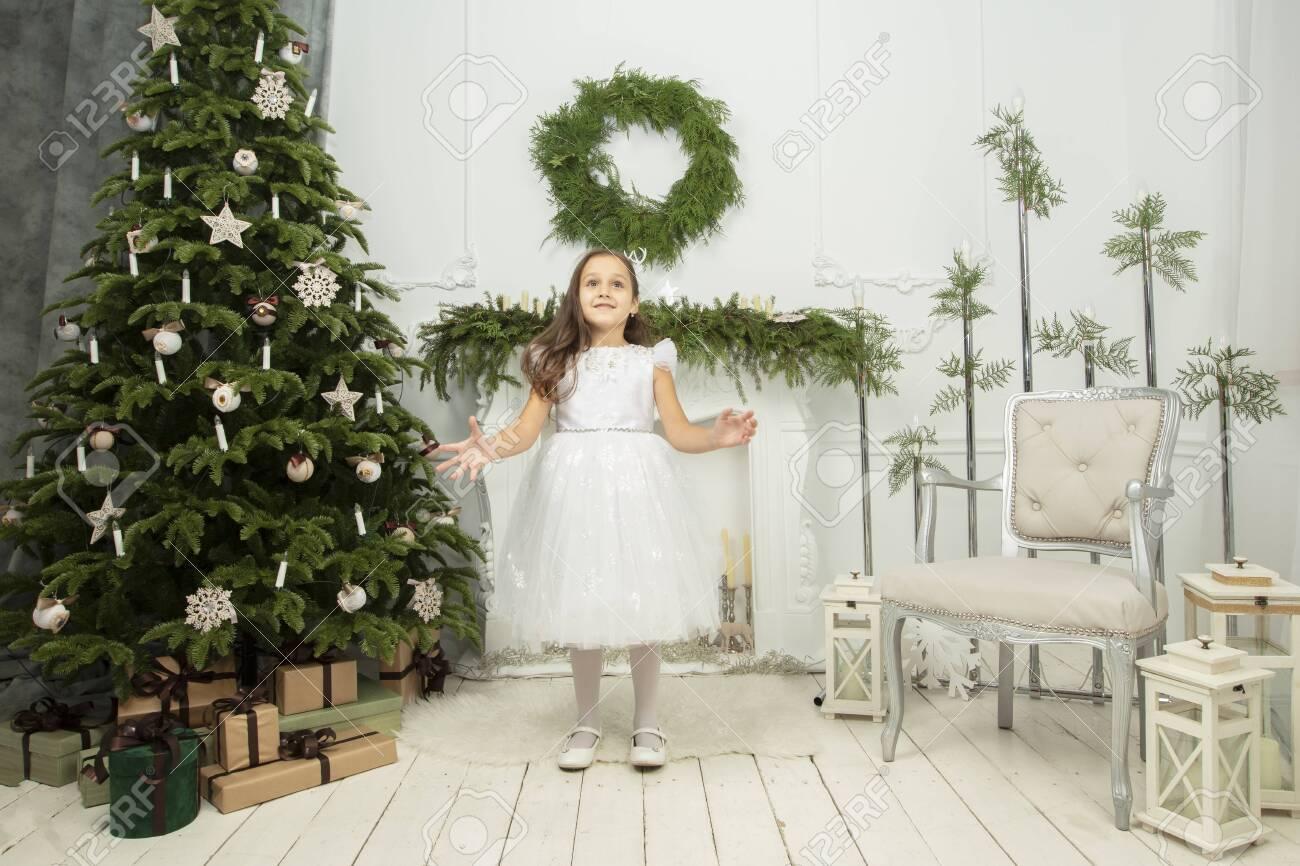 Elegant child at the Christmas tree. Little joyful girl in christmas - 156394433