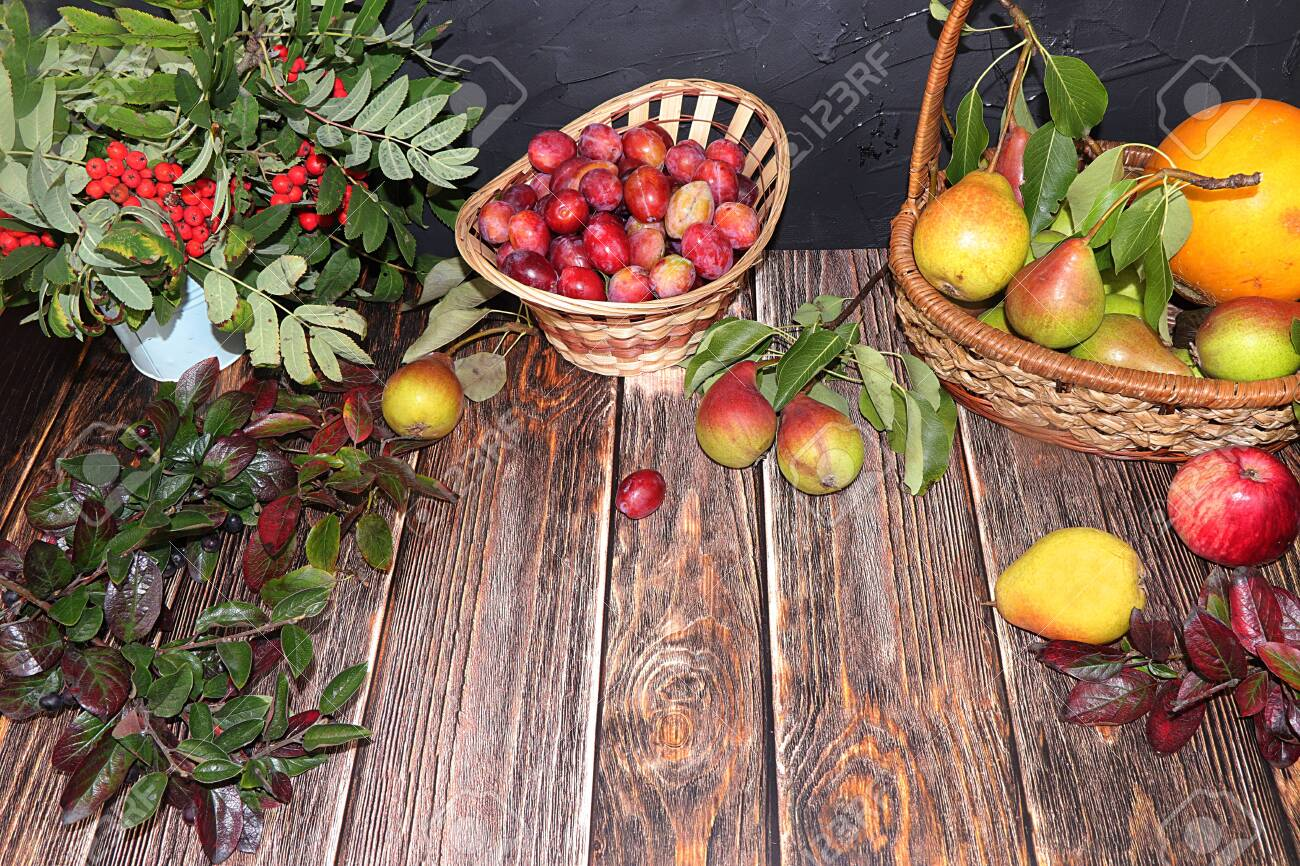 Cup of hot tea and dessert on an autumn wooden table with vegetables and fruits on a wooden table with leaves, flat lay, top view ,. Cosiness and comfort in the house in the cold autumn, harvesting and the approaching winter - 130985621