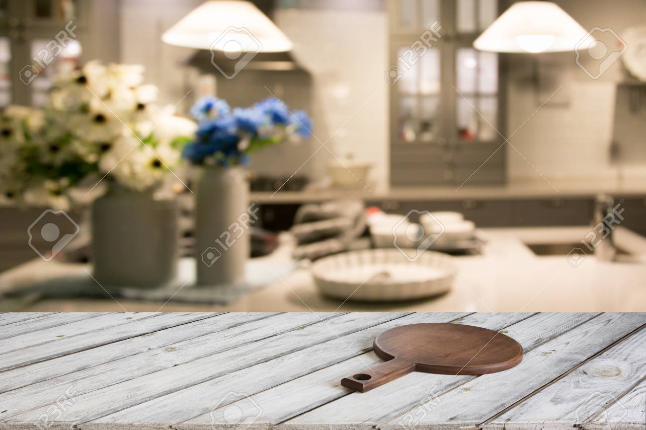 Tagliere Per Piano Cucina sfocato e astratto cucina sfondo. tavolo in legno vuoto con tagliere e  cucina moderna defocused per la visualizzazione o il montaggio dei vostri