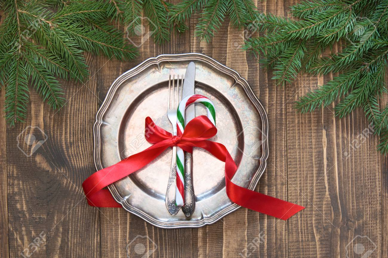 christmas table setting with candy cane and red ribbon as decor vintage dishware silverware