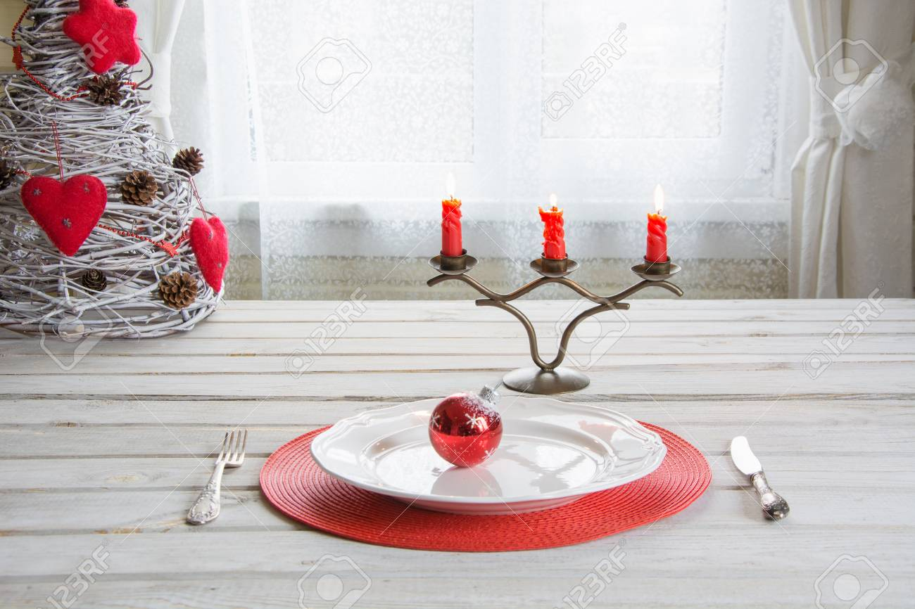 Christmas Place Setting With White Dishware, Cutlery, Silverware And Red  Decorations On White Wooden