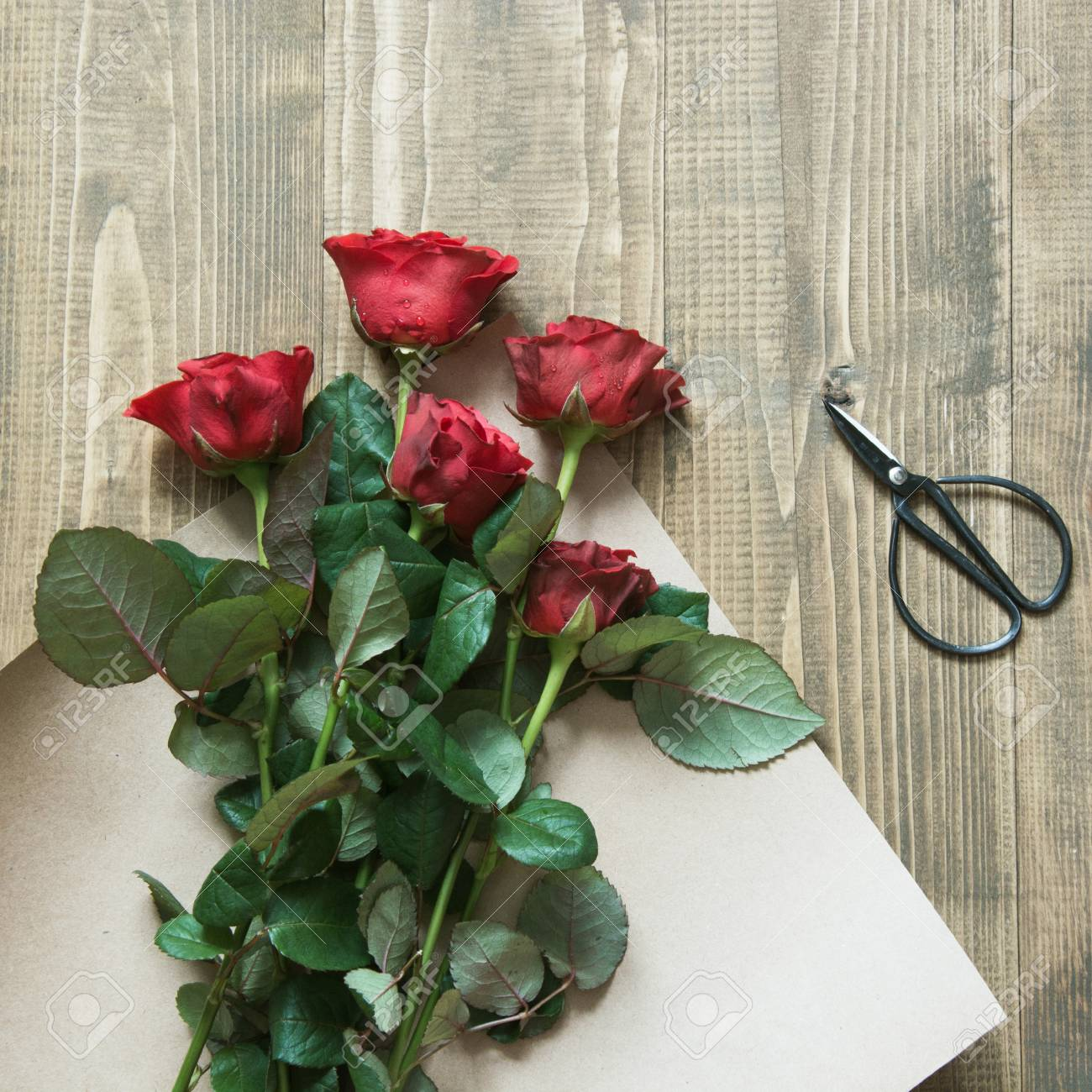 Florist Making A Red Roses Bouquet Wrapping In Kraft Paper On