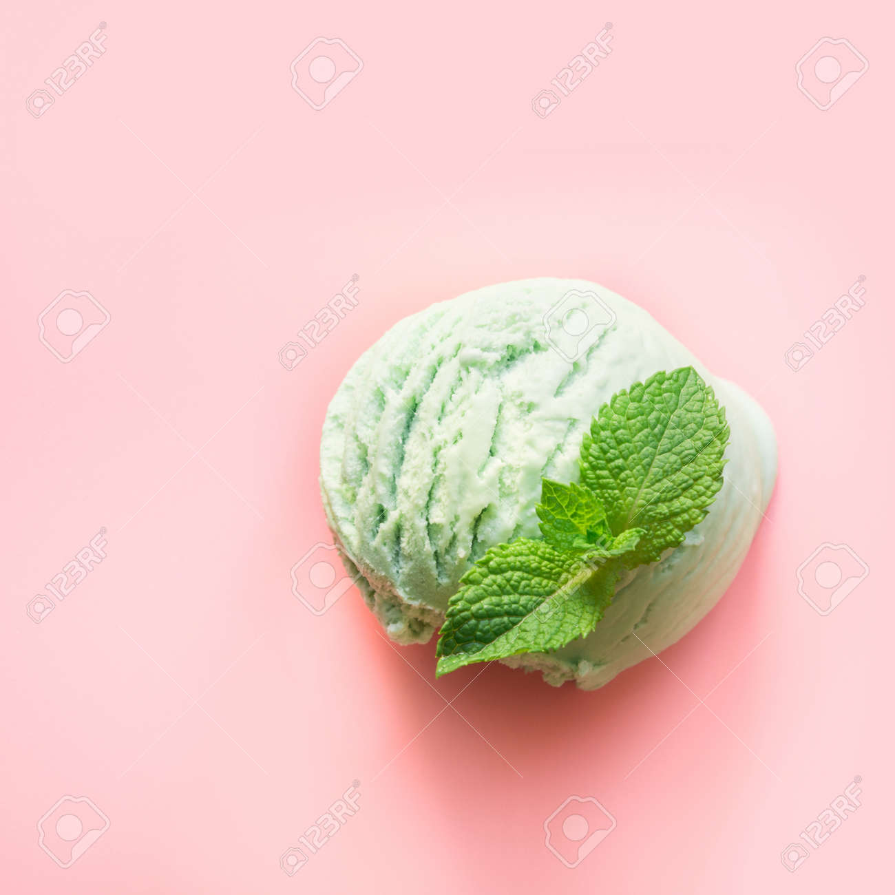 One green pistachio or matcha tea ice cream ball with mint on pink background. - 126572846