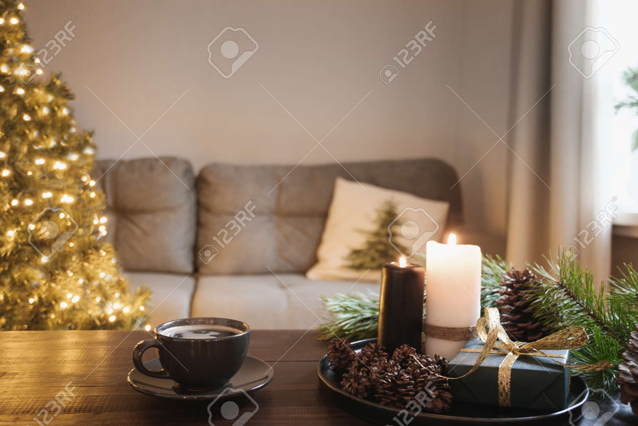 Cozy interior with Christmas tree and warm cup of coffee on wooden tabletop with candles, gifts cones in living room. Xmas holiday at home. - 159605585