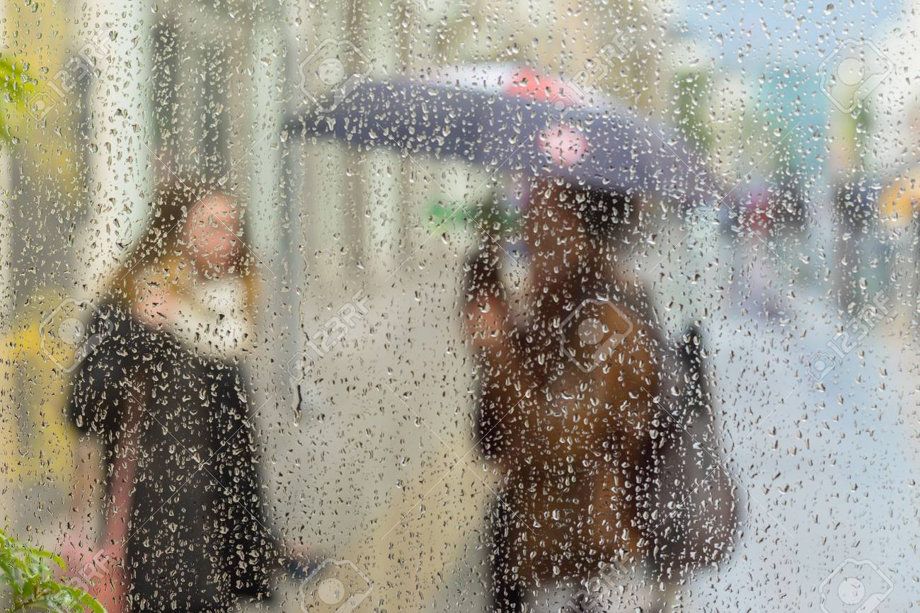 Abstract Blurred Silhouettes Of People With Umbrellas On Rainy Day In City Two Girls Seen