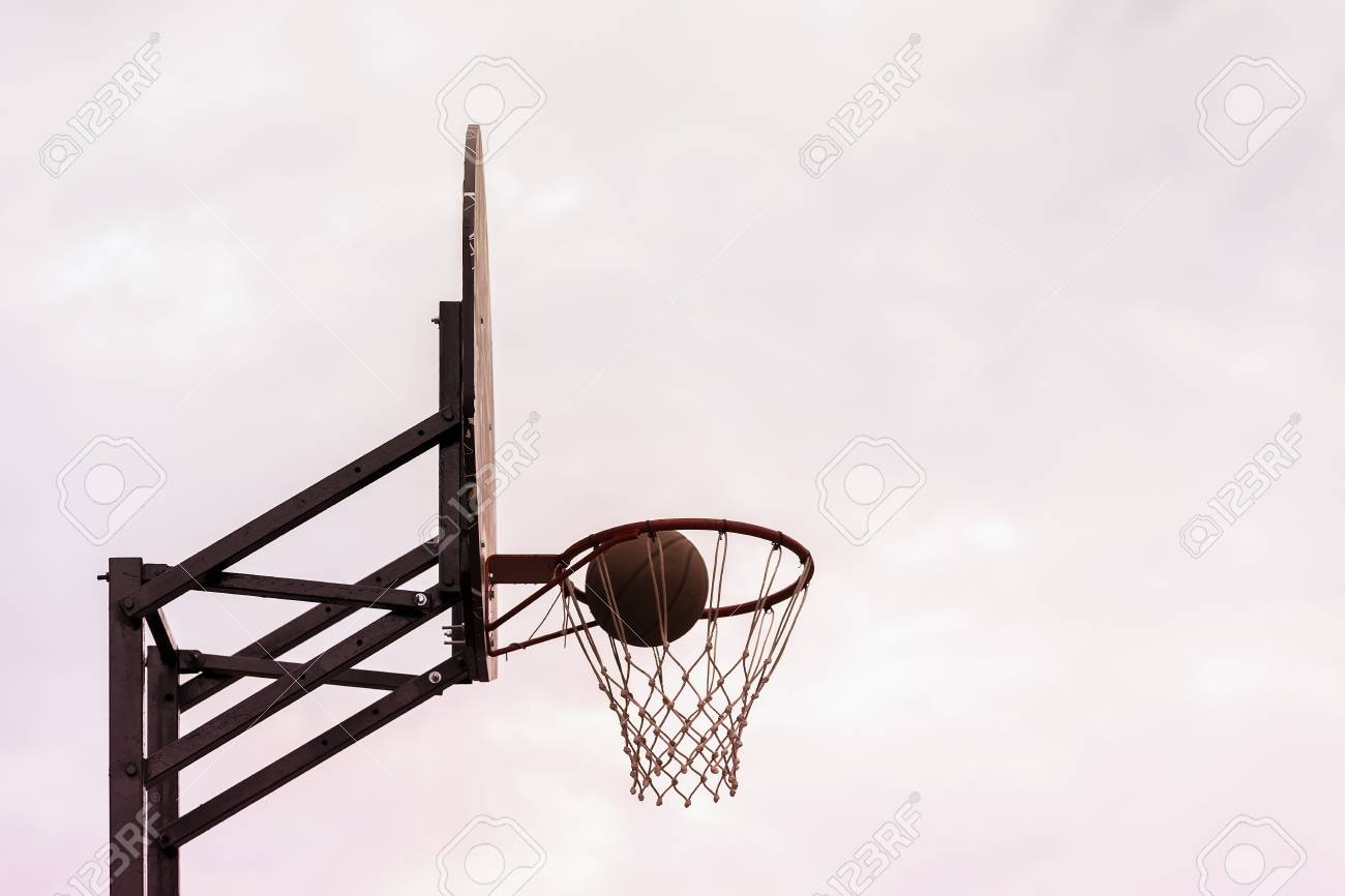 basketball shield ball going through basket on background of