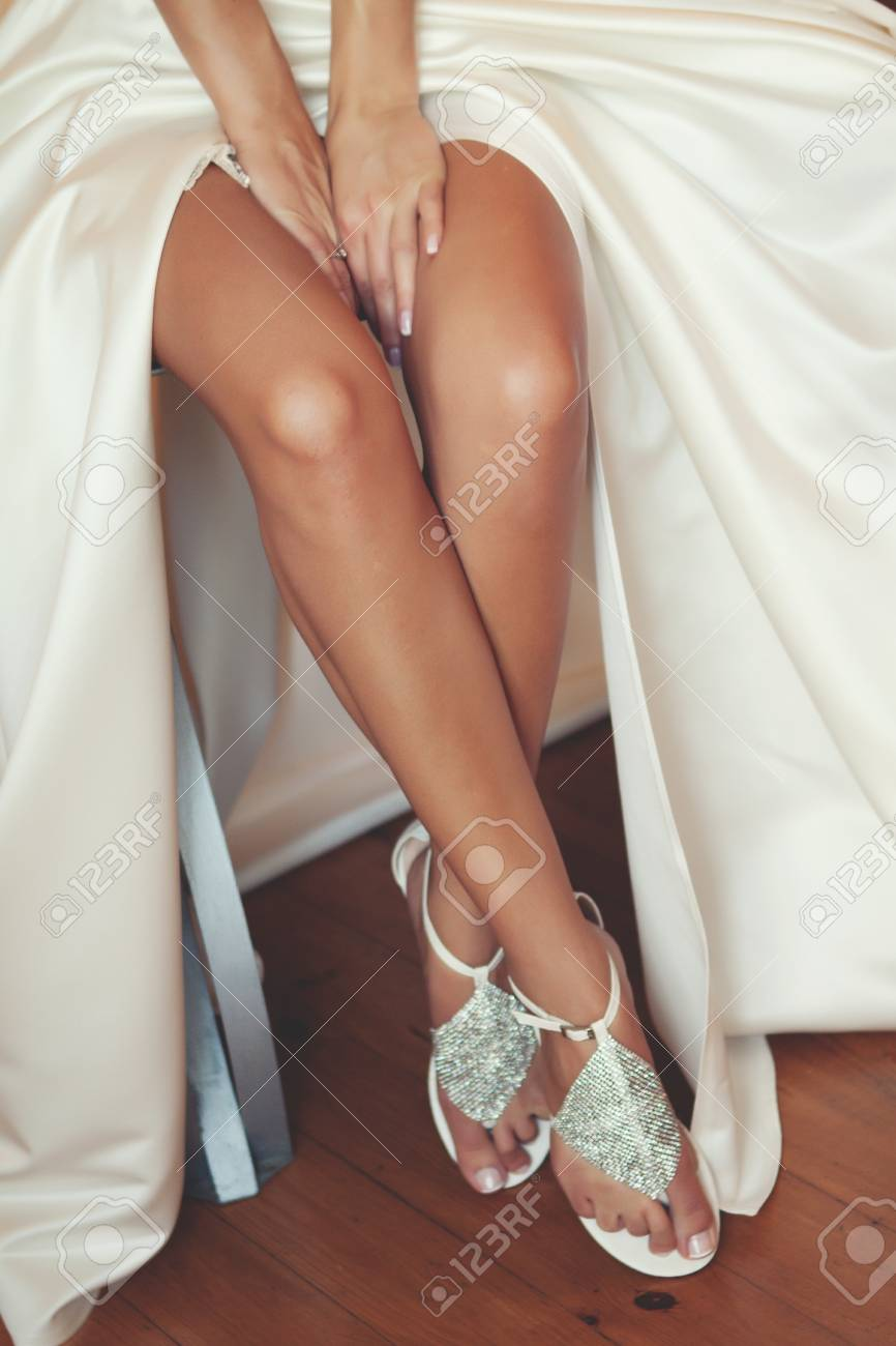 Legs Of The Bride In A Beautiful Wedding Dress Sandals Of The