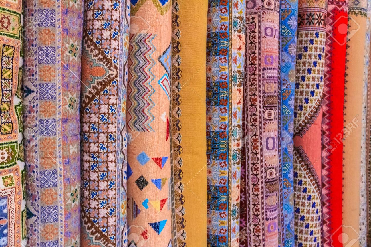 Pile de tapis d\'Afrique du Nord dans les tons rouge, orange et marron, à  Fès, au Maroc.