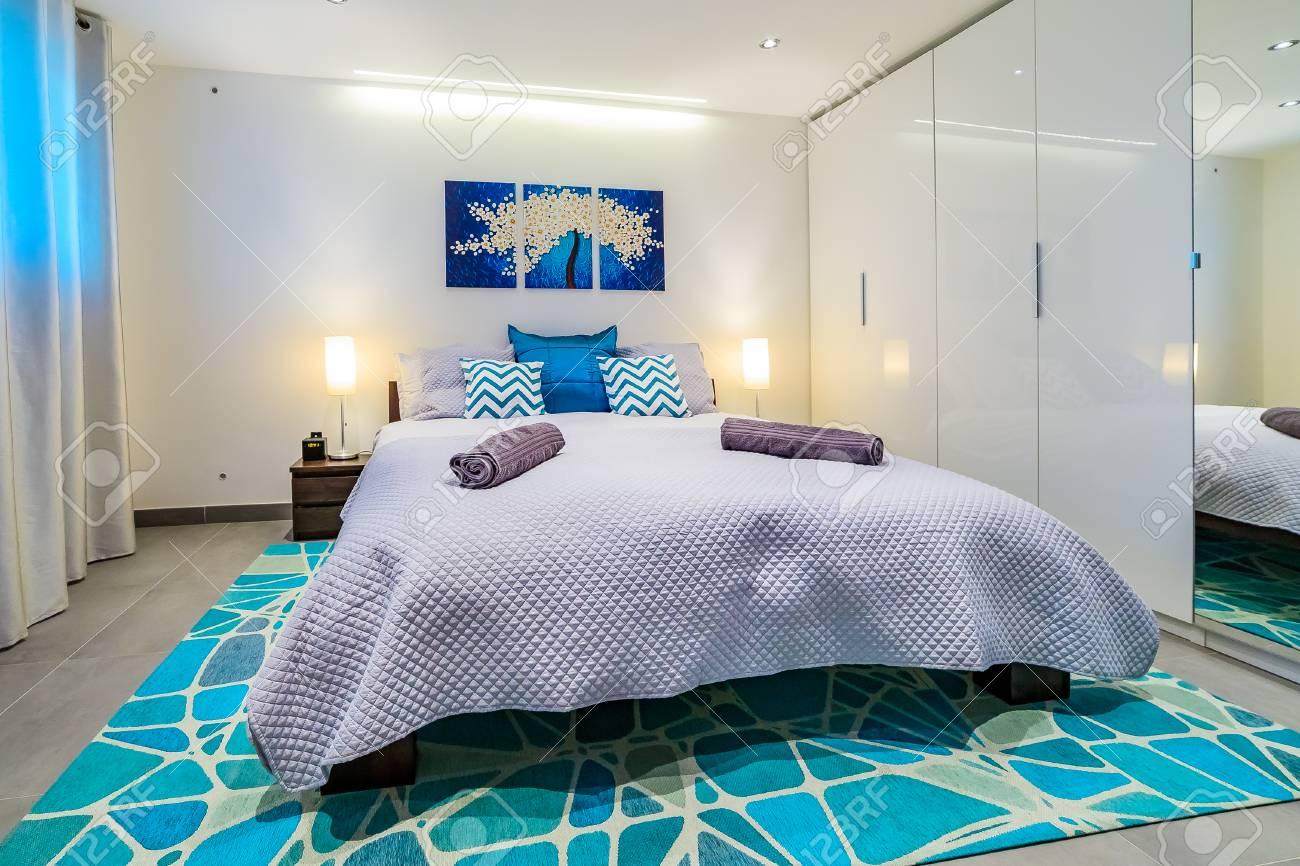 Grand lit avec des draps et des oreillers bleus lumineux dans une chambre à  coucher moderne, peinture murale et des lumières