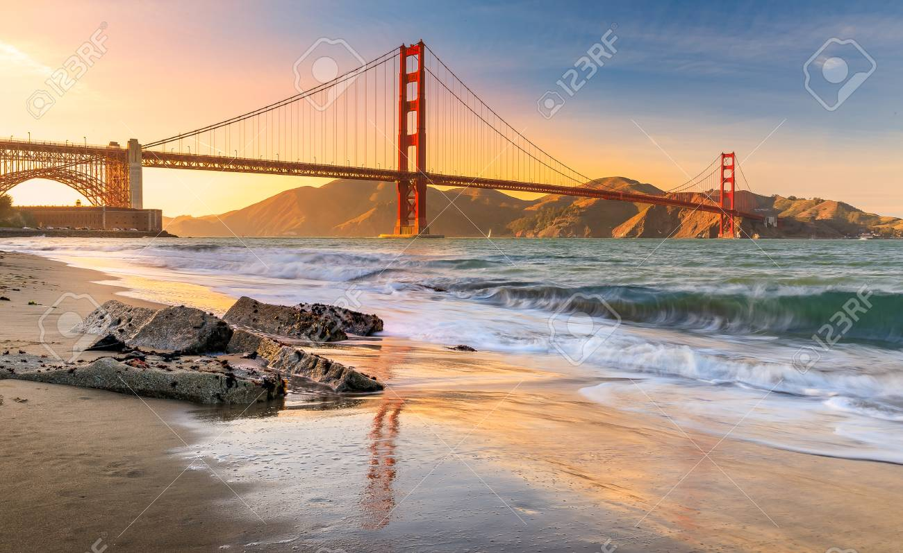 Long exposure of a stunning sunset at the beach by the famous Golden Gate Bridge in San Francisco, California - 96710636