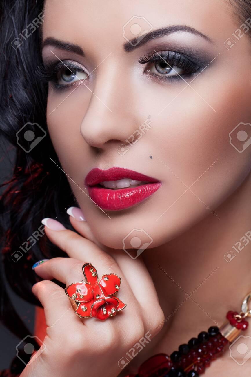 Close-up Portrait der schönen Brünette mit Schönheitsfleck tragen rote  Lilie Ring