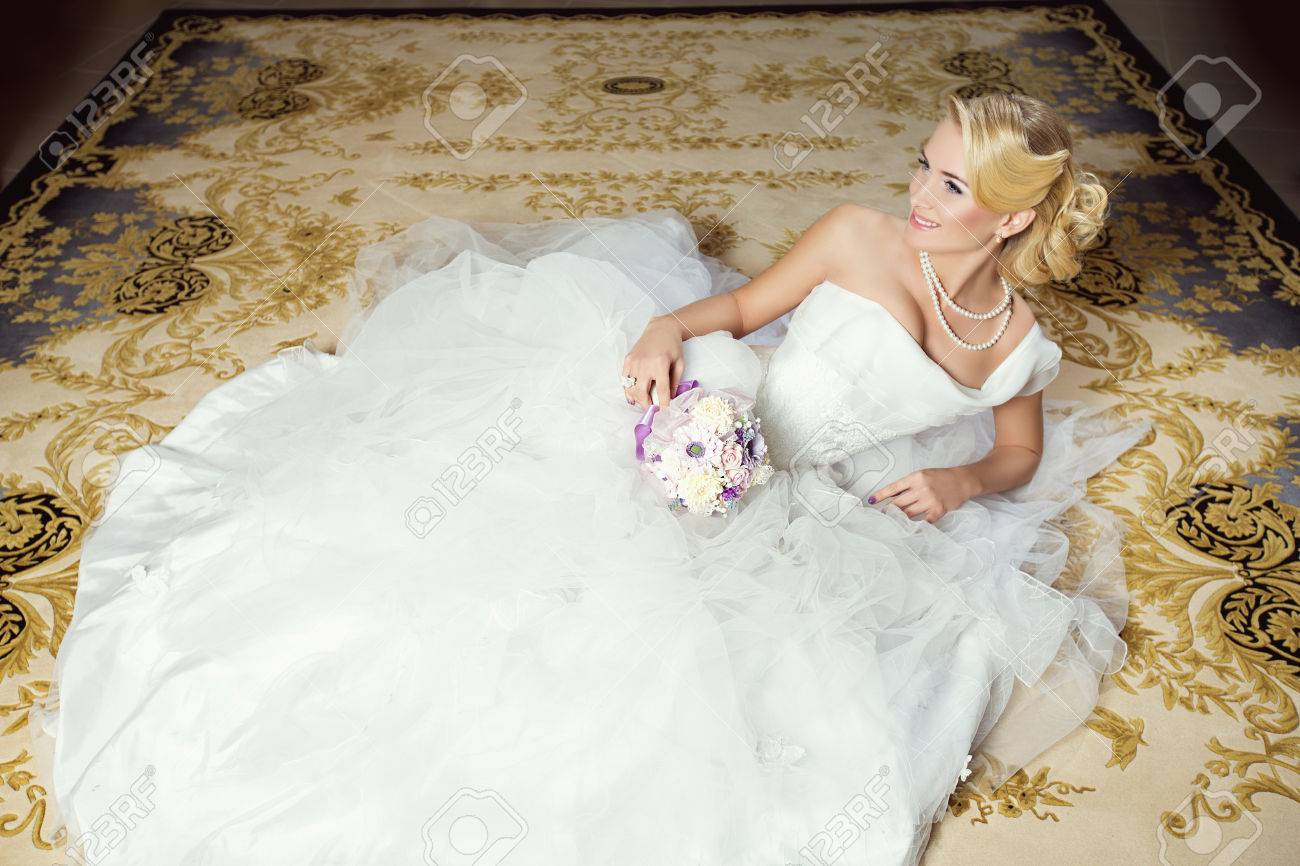 Beautiful young bride in white fluffy dress lying on carpet - 39543574