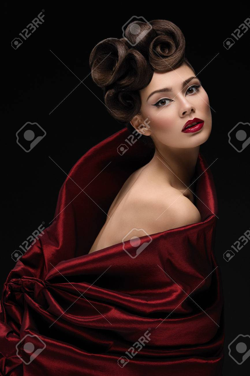 Beautiful young woman with fashionable hairstyle and makeup in red textile looking like tulip - 40804251