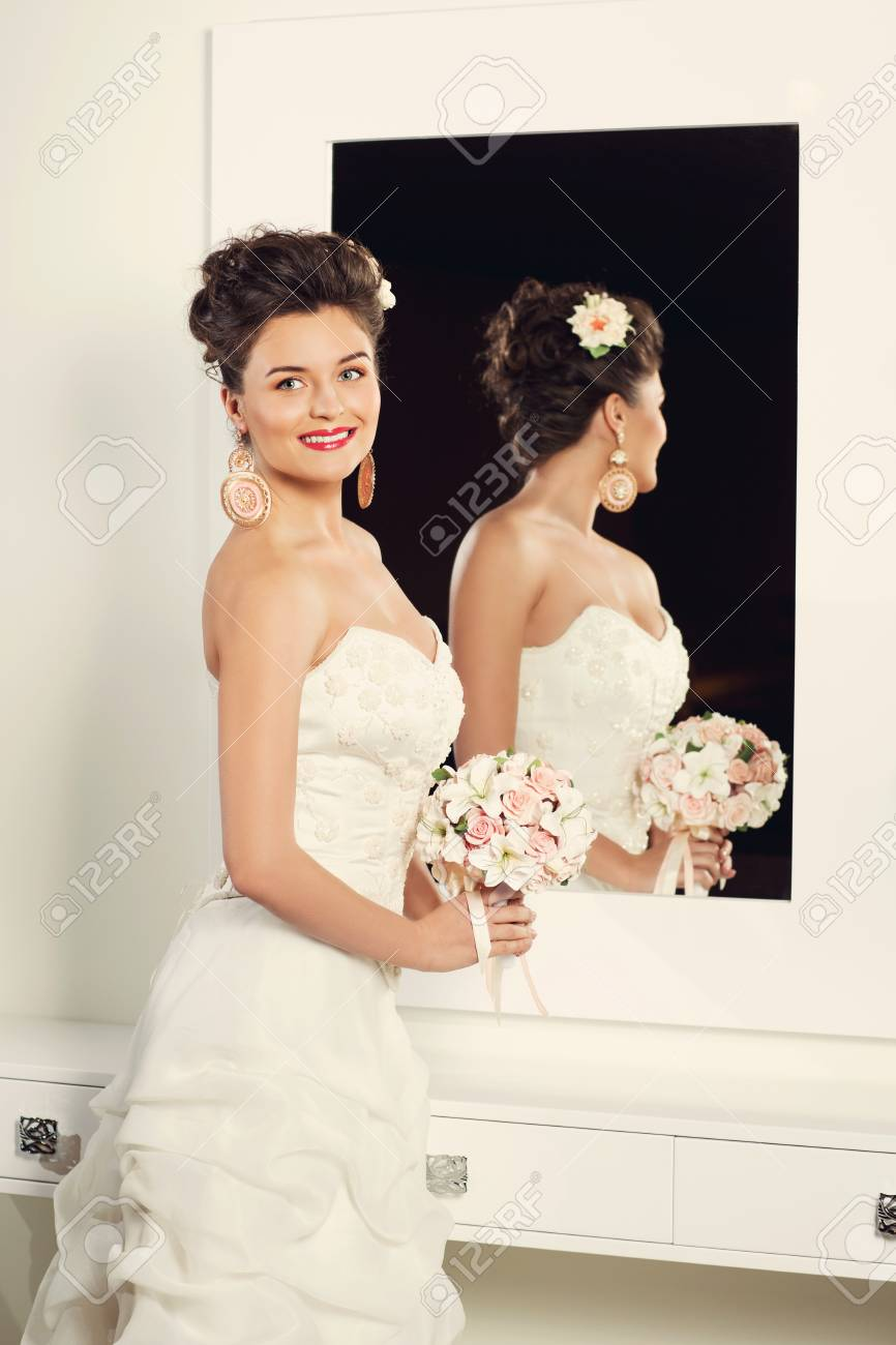 Schone Junge Braut Im Stilvollen Hochzeitskleid Das Nahe Spiegel