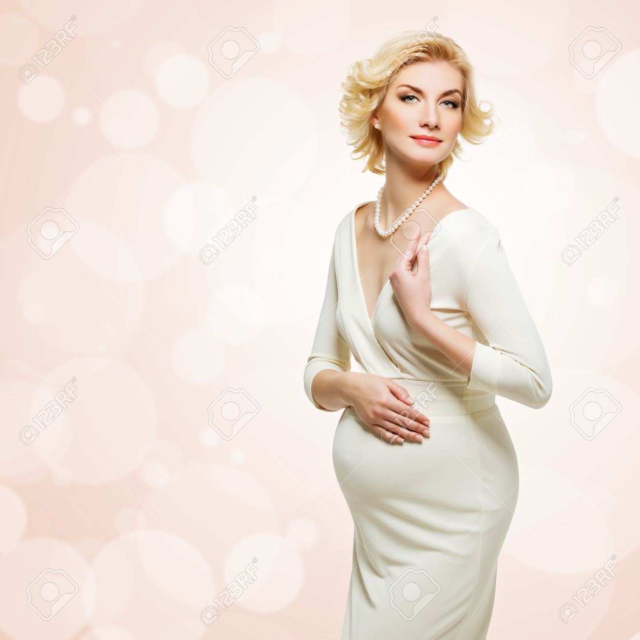 6e85294bf2 Bella elegante giovane donna incinta, che indossa bianco abito lungo in  piedi sopra la priorità bassa di corallo con bokeh. Copia spazio. Isolato.