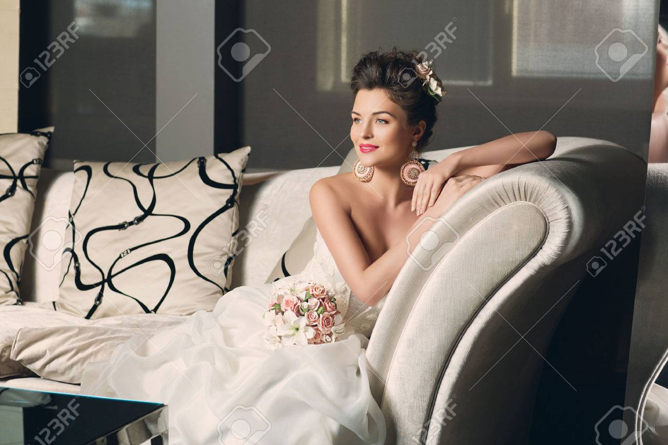 Beautiful young bride in fashionable gown with sitting on sofa. Interior photo. - 41867809