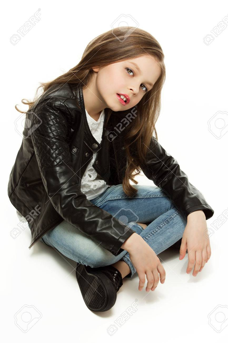 Little girl in fashion leathet jacket and jeans sitting on floor. Isolated over white background. - 43550347