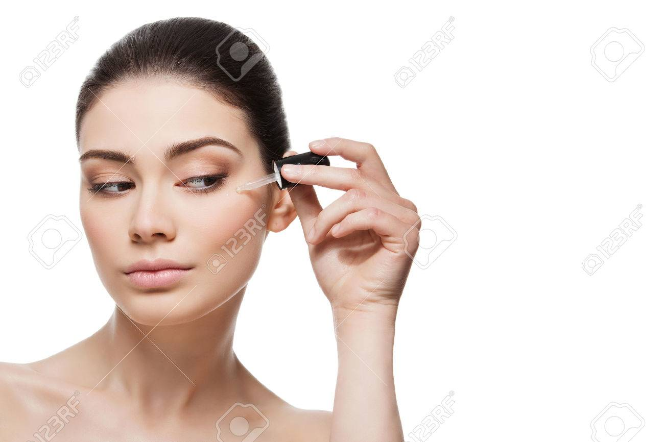 Beautiful young woman applying anti-ageing moisturizing serum to under eye area. Isolated over white background. Copy space. - 44387741