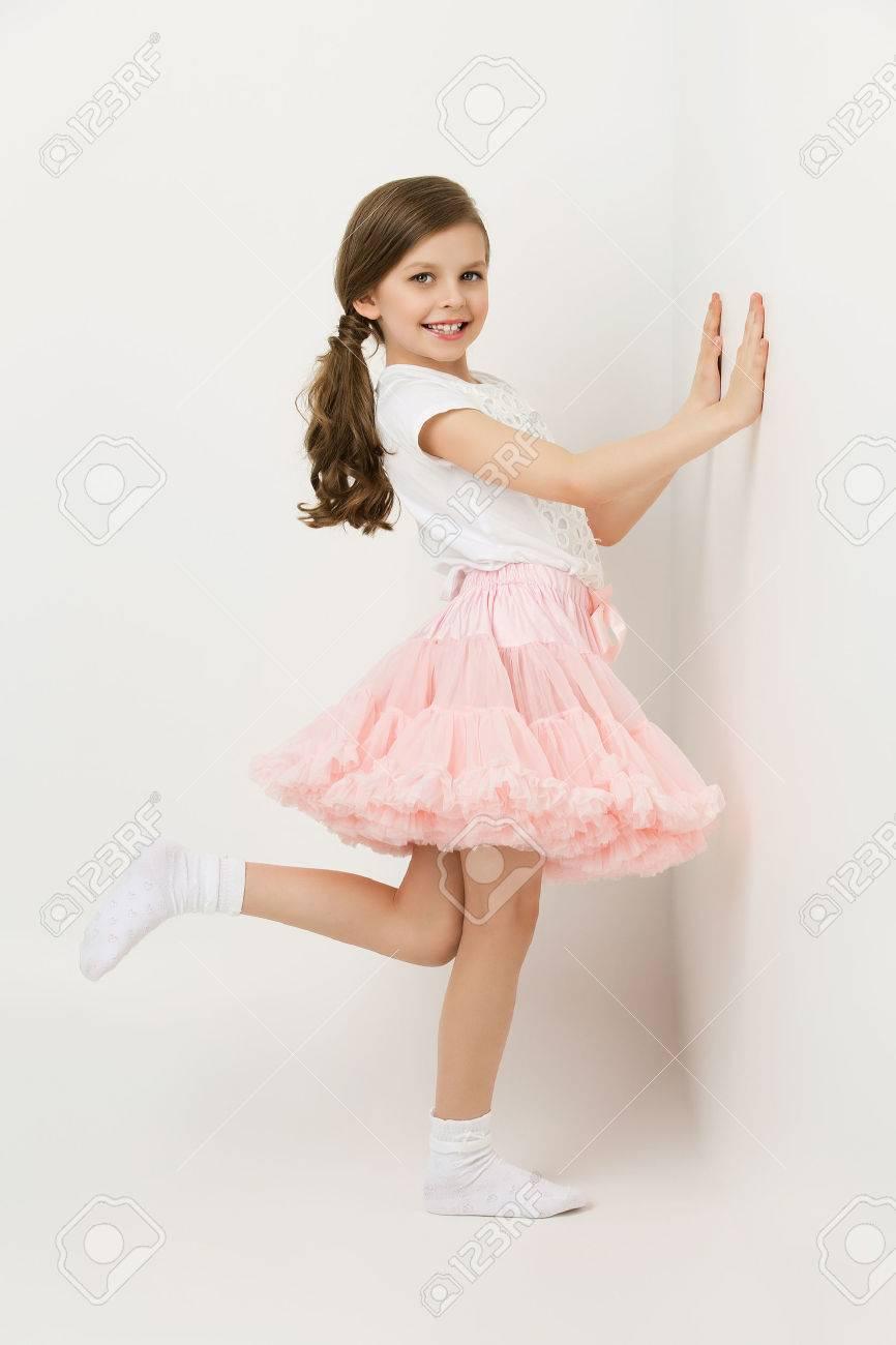 Beautiful little happy girl in tutu skirt standing near white wall - 46427965