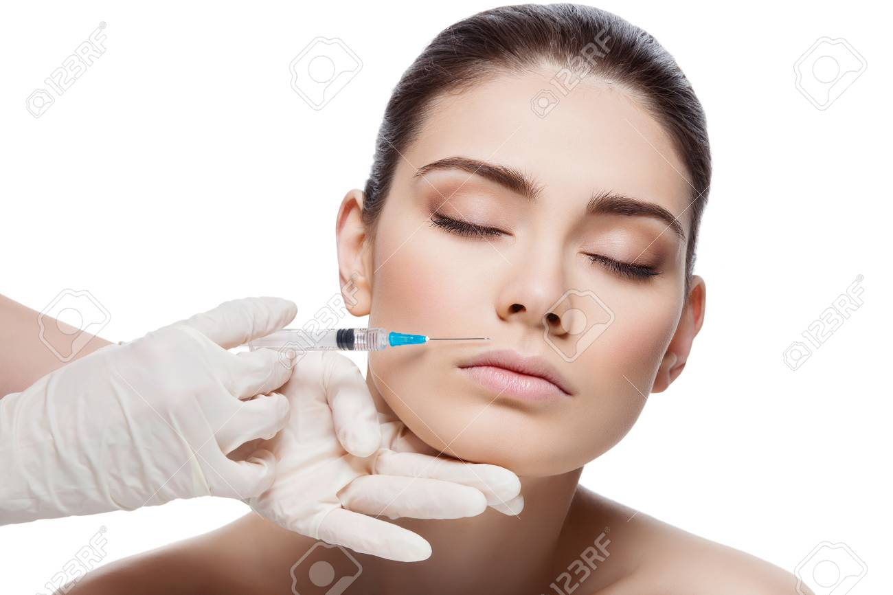 Beautiful young woman gets beauty injection in lips from sergeant. Isolated over white background. - 47627047
